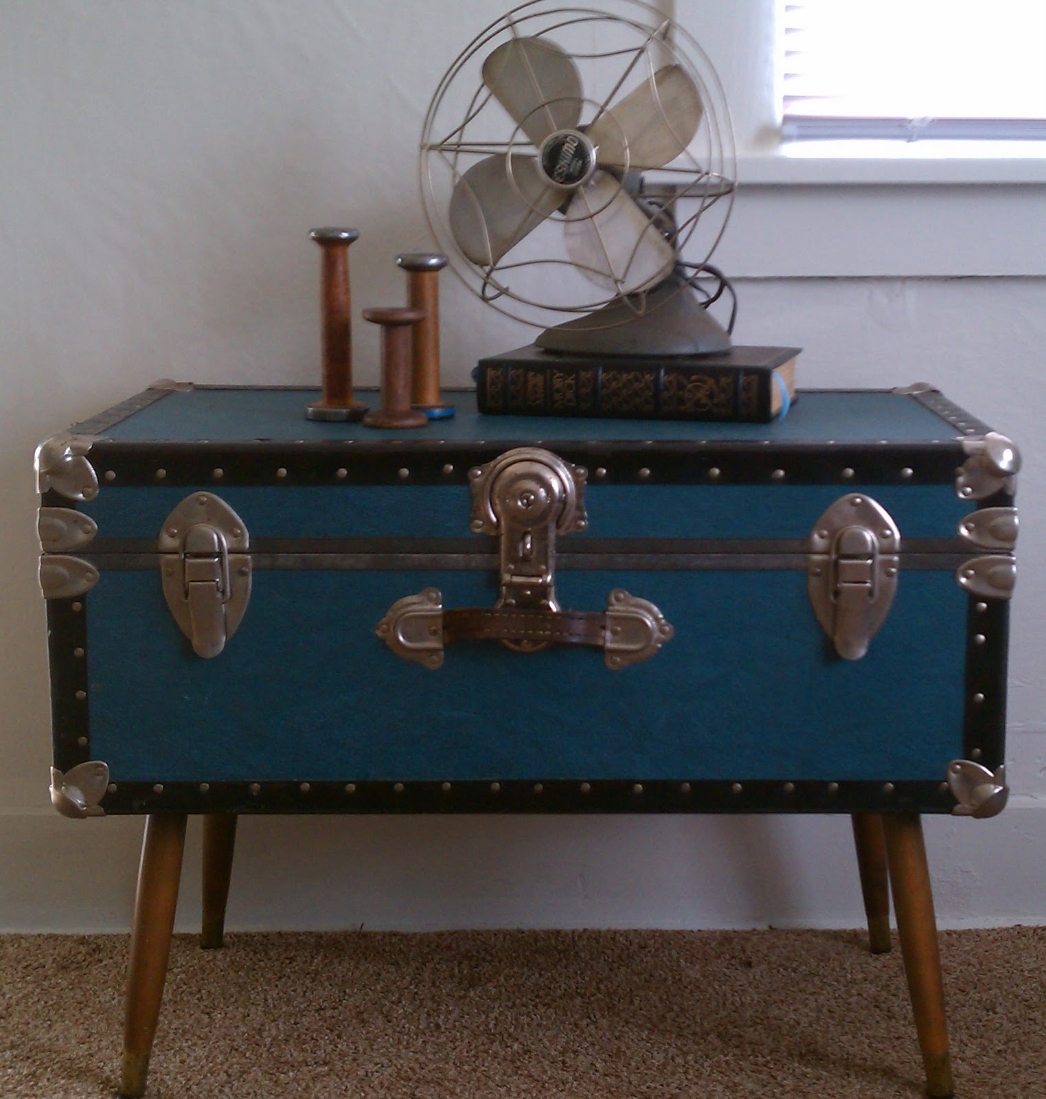 Low stand fan on steamer trunk coffee table in bedroom with beige carpeting wicker trunk coffee Trunks coffee tables